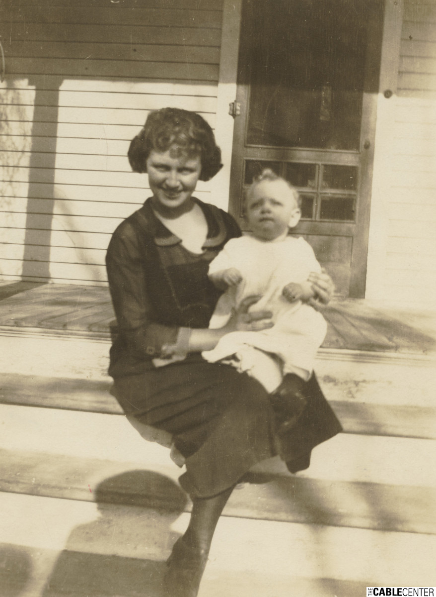 Bill Daniels' mother Adele holding Bill on the porch of their home in Greeley in March 1921