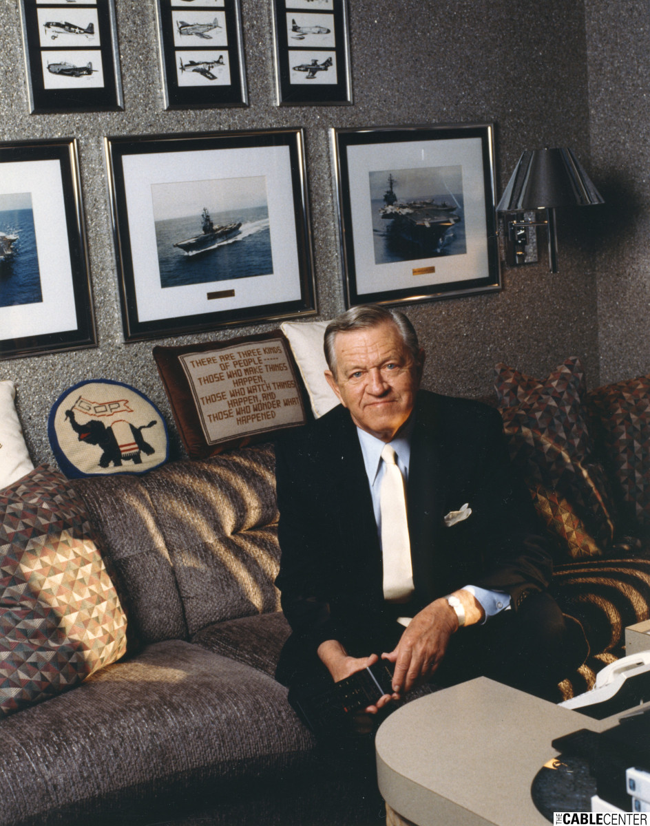 "Bill Daniels seated on couch in his residence ""Cableland;"" pictures of the carriers he served on and Navy planes he flew in the background. Daniels Collection  [Relentless, p. 200]"