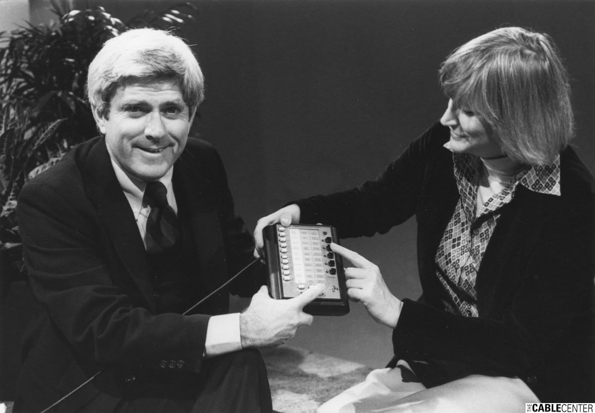 Phil Donahue and Vivian Horner demonstrate a QUBE interactive set-top box.