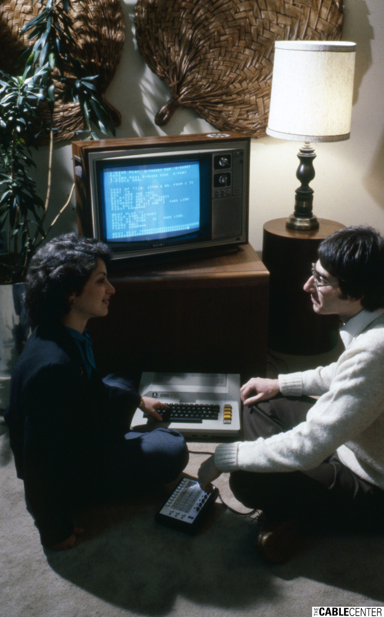 Couple plays a text-based football game on their QUBE-equipped television with an Atari 800 computer