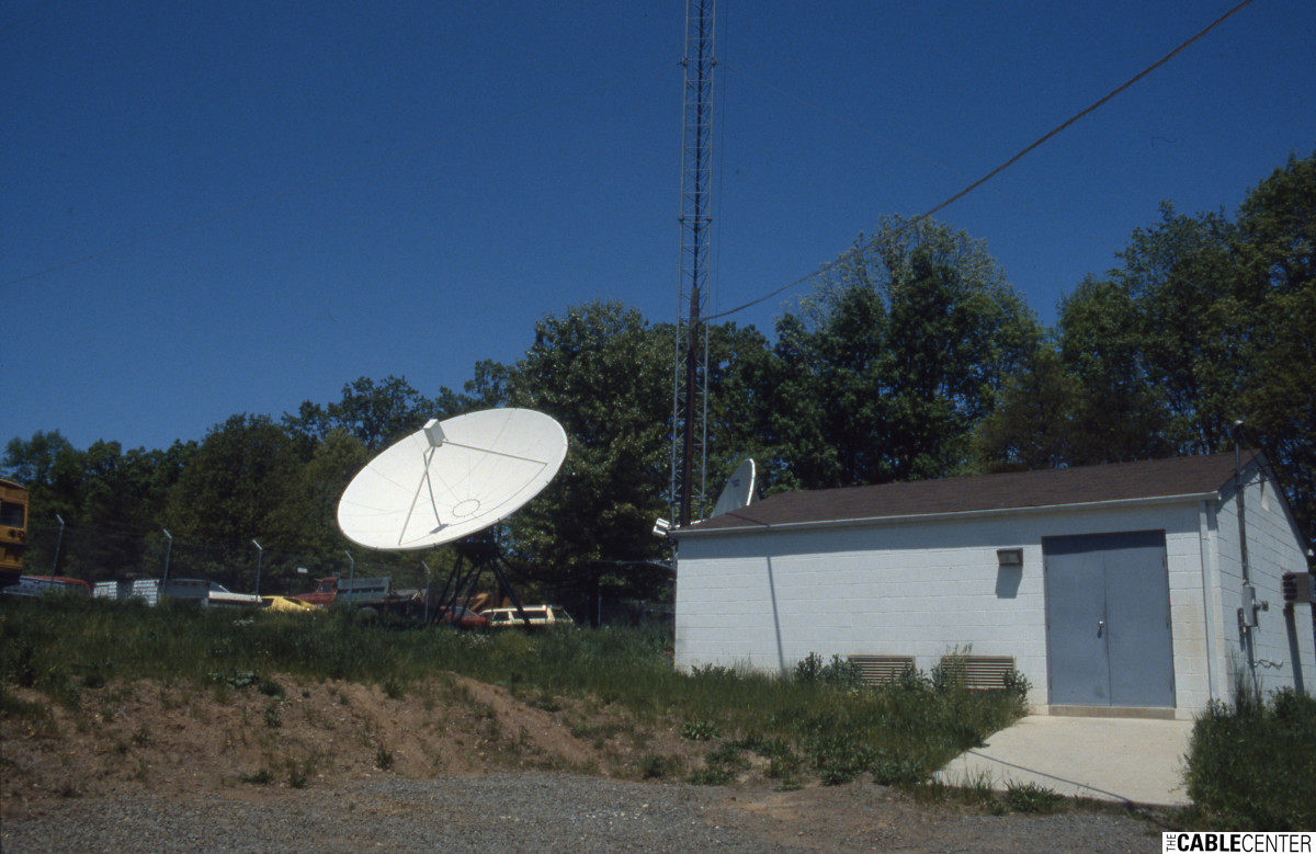 Satellite dish antenna installed next to antenna tower and building.