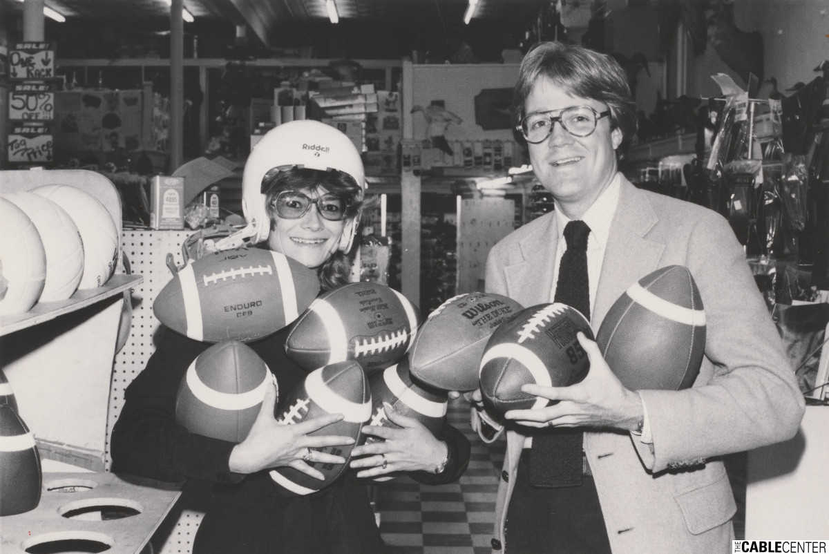 Bill Grumbles of HBO and unidentified woman holding footballs in a sporting goods store