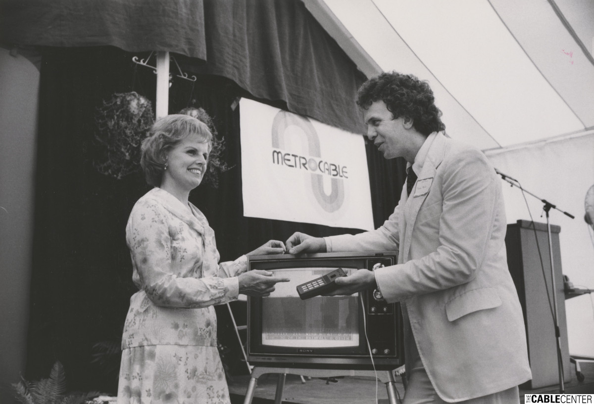 Metrocable's charter subscriber in Washington DC ,Jean Jenstrom, is shown a corded remote control by Richard Howe at launch ceremony