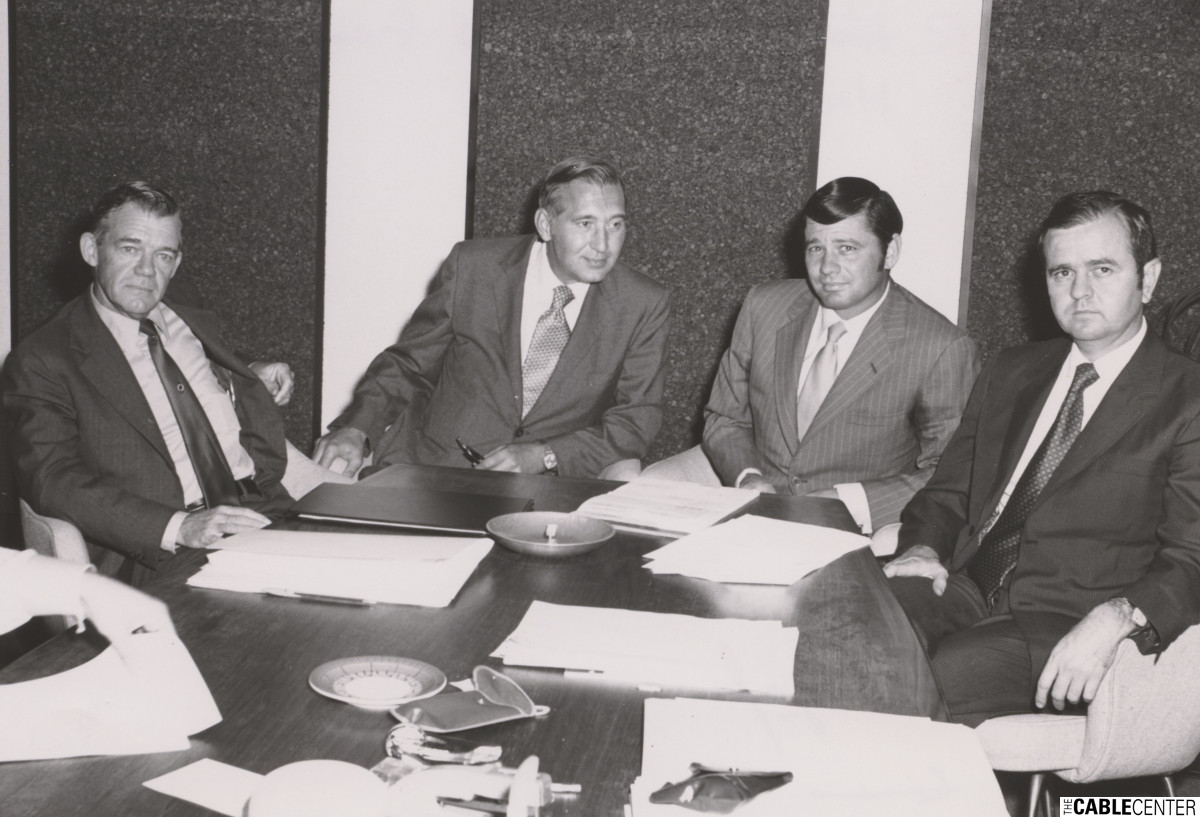 Alan Harmon sitting with unidentified men