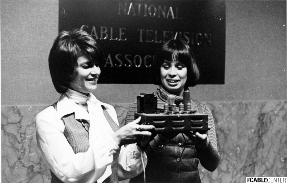 Two women pose with a piece of cable television equipment