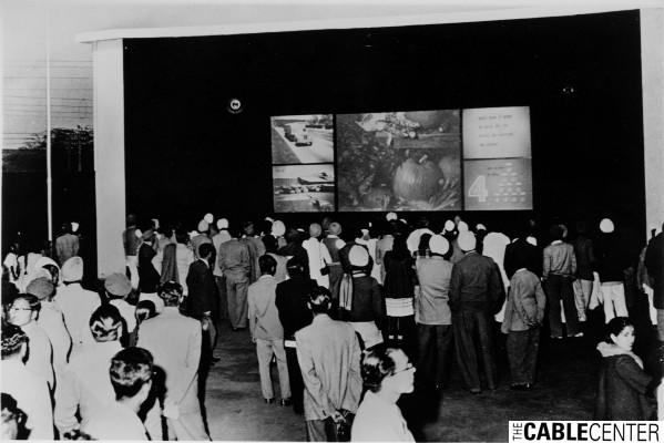 Crowd watches TelePrompTer rear-projection television demonstration in New Delhi