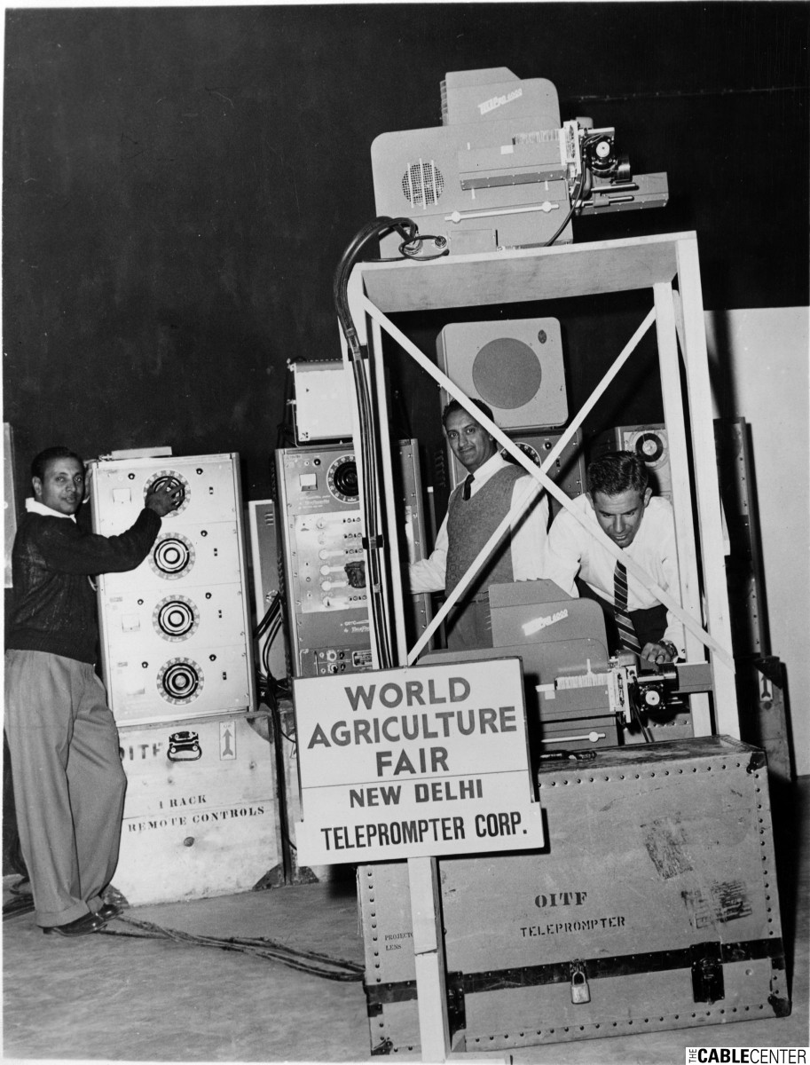 Technicians pose with TelePrompTer rear-projection television equipment