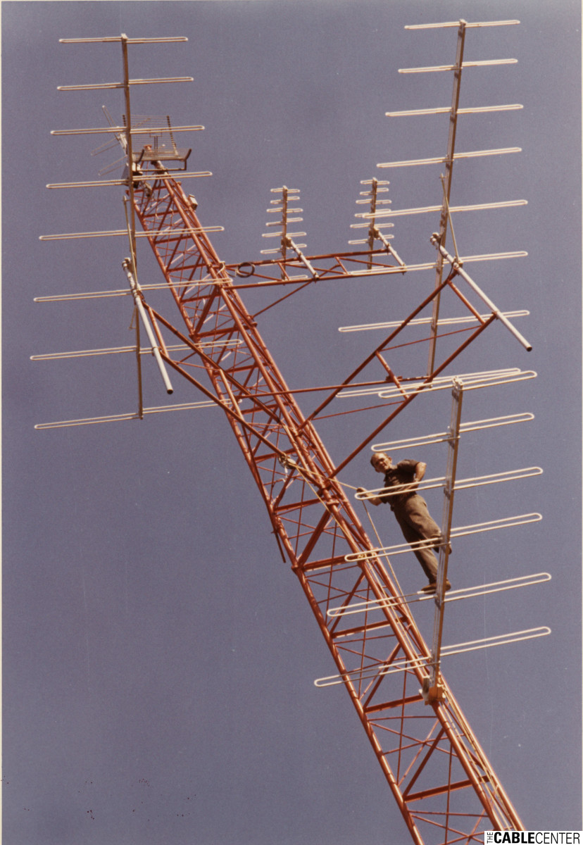 Man perched on antenna tower