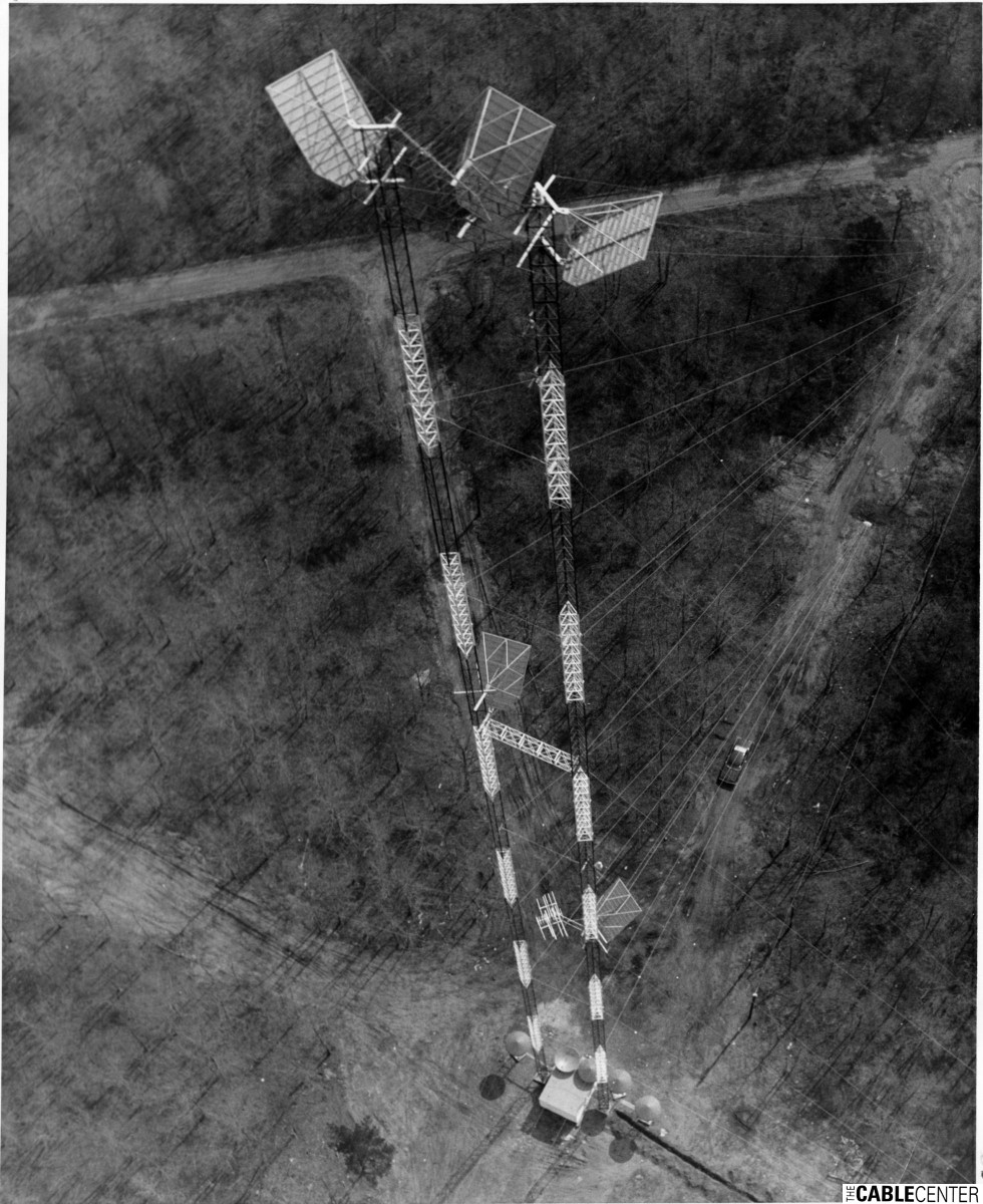 Aerial view of antenna tower with microwave dishes at base