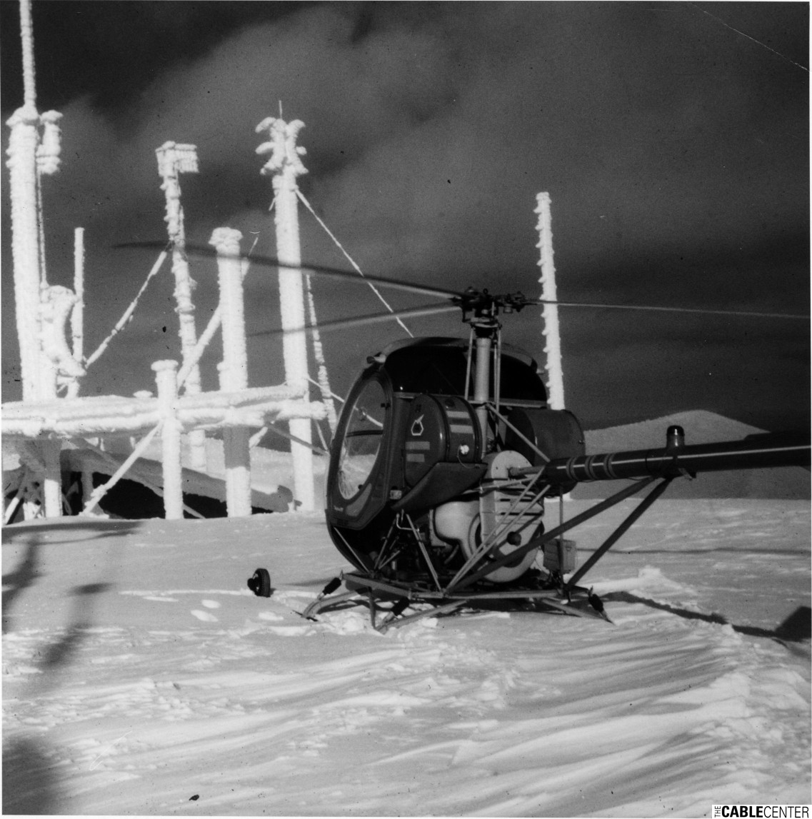 Helicopter parked in front of iced-over antenna equipment