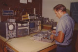 Cable television technician works on amplifier on test bench
