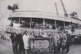 Home Box Office Super Bowl contest winners pose with HBO Sports banner in front of a steamboat in New