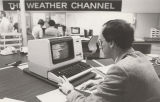 The Weather Channel employees at a computer in the production studio
